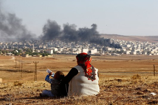 Turkish Kurds watch smoke rises over Syrian town of Kobani after an airstrike, as seen from the Mursitpinar border crossing on the Turkish-Syrian border